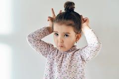Närbildståenden av nätta gulliga flickor behandla som ett barn med hår samlad nolla Royaltyfria Bilder