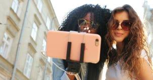 Närbildståenden av två charma le flickor som överför luft, kysser, medan göra selfie Ett av dem är afro--amerikanen lager videofilmer