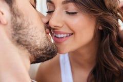 Närbildståenden av två vänner kopplar ihop att kyssa arkivbild
