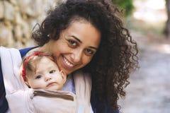 Närbildståenden av ungt attraktivt bära för moder behandla som ett barn i en rembärare arkivfoto