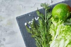 Närbildstilleben av blandade nya grönsaker och örter på vit texturerade bakgrund, den bästa sikten, selektiv fokus Arkivbilder