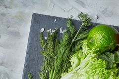 Närbildstilleben av blandade nya grönsaker och örter på vit texturerade bakgrund, den bästa sikten, selektiv fokus Fotografering för Bildbyråer