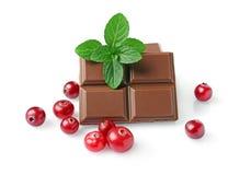 Närbildstycken av mjölkar chokladstången med den nya tranbäret och mintkaramellen royaltyfri foto