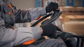 Närbildstyrninghjul och spakar Man körning av en gaffeltruck till och med ett lager i en fabrik chaufför i likformig och