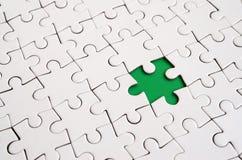 Närbildtextur av ett vitt pussel i församlat tillstånd med missande beståndsdelar som bildar ett grönt block för text kopiera avs arkivfoto