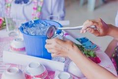Närbildthhänder tillfogar is till exponeringsglaset för att fördela till vänner royaltyfria foton