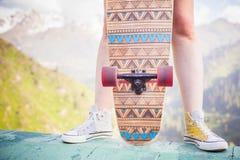 Närbildtonåringanseende med skateboarden som är utomhus- på berget Arkivbild
