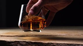 Närbildultrarapidhand som rymmer en exponeringsglasbägare med whisky arkivfilmer