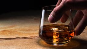 Närbildultrarapidhand som rymmer en exponeringsglasbägare med whisky stock video