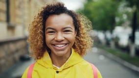 Närbildultrarapidstående av den attraktiva flickan för blandat lopp som ser kameran med det lyckliga leendet som uttrycker realit lager videofilmer
