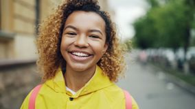 Närbildultrarapidstående av den snygga afrikansk amerikankvinnan som ser kameran med glat leende och att skratta stock video