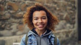 Närbildultrarapidståenden av att le afrikansk amerikantonåringen i grov bomullstvill beklär att se kameran och att posera Lycklig arkivfilmer