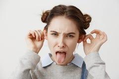 närdu ser kvinnan som fram bär tillfällig grimacing med tungan som gör ut, gå i ax att sticka stäng upp kvinnligståenden royaltyfri bild