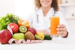 Näringsfysiolog som främjar sunt äta, erbjudande orange fruktsaft arkivbilder