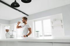 Näringtillägg Man som dricker proteinskakan för genomkörare royaltyfria bilder