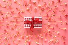 Närvarande ask med den röda pilbågen på rosa liten blommabakgrund Royaltyfri Foto