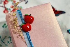 Närvarande ask med röda äpplen och en strumpebandsorden Arkivbilder