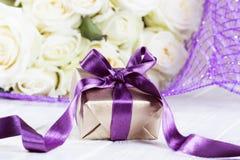 Närvarande gåvaask steg blommor och gåvaasken med bandet på ligh Arkivfoto
