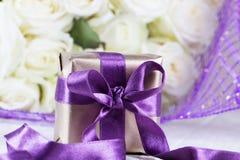 Närvarande gåvaask steg blommor och gåvaasken med bandet på ligh Royaltyfri Fotografi