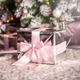 Närvarande julask med det mjuka rosa bandet arkivbilder