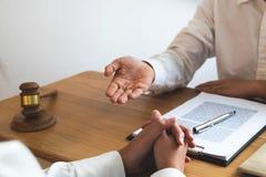 Närvarande klient för advokat med avtalslegitimationshandlingar på tabellen i regeringsställning konsulentadvokat, advokat, domst arkivbild
