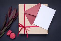 Närvarande kort och gåva i ask med satängbandet på mörk bakgrund arkivfoton