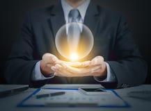 Närvarande kristallkula för affärsman på händer Arkivbilder