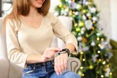 Närvarande nytt år för flickvänprovningssmartwatch i hemtrevligt rum Fotografering för Bildbyråer