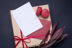 Närvarande vitt kort och gåva i ask med satängbandet på mörk bakgrund royaltyfri fotografi