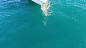 Näsan av en liten segla yacht som förtöjas med ett vitt rep i hamnen materiel Framdelen av den vita yachten på arkivbilder
