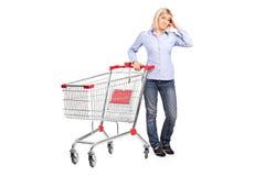 nästa posera shopping för bankruttt vagn till kvinnan Arkivfoto