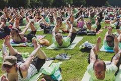 Nästan 2000 personer tar en fri kollektiv yogagrupp i en stad parkerar i Milan, Italien Royaltyfri Fotografi