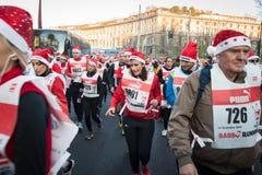 Nästan 10,000 Santas tar delen i den Babbo springen i Milan, Italien Arkivbilder