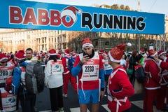 Nästan 10,000 Santas tar delen i den Babbo springen i Milan, Italien Arkivbild