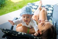 Nätt älska mamma som försöker att lugna scarred gråt för att behandla som ett barn i moders armar som är utomhus- på solsolstol arkivfoton