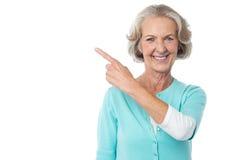 Nätt åldrig kvinna som pekar på något Royaltyfri Foto