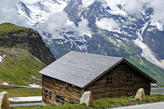 Nätt österrikiskt hus med den storartade sikten av fjällängarna Arkivfoto
