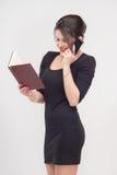 Nätt affärsdamanseende med boken Arkivbild