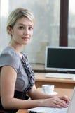 Nätt affärskvinna med anteckningsboken i kontoret arkivfoto