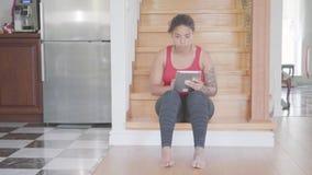 Nätt afrikansk amerikankvinna som sitter på trappan på det första golvet av det stora huset som smsar på hennes minnestavla confu lager videofilmer