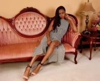 Nätt afrikansk kvinna på rosa färgsoffan royaltyfria bilder
