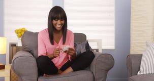 Nätt afrikansk kvinna som hemma använder smartphonen arkivbilder