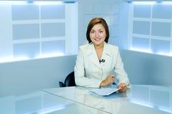 Nätt anchorwoman på den ljusa TVstudion Arkivbild