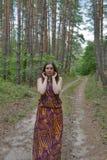Nätt anseende för ung kvinna på skogvägen Fotografering för Bildbyråer