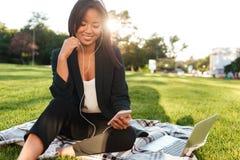 Nätt asiatisk affärskvinna och att prata på mobiltelefonen, sittande nolla Royaltyfri Fotografi