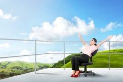 Nätt asiatisk affärskvinna som sitter på stolen och kopplar av på terrassen royaltyfri foto
