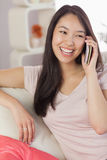 Nätt asiatisk flicka som talar på hennes smartphone på soffan Royaltyfria Bilder