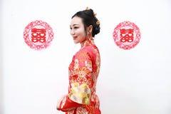 Nätt asiatisk kinesisk härlig brud med den traditionella kinesiska röda klänningen för bröllop och dubbel lycka två royaltyfri fotografi