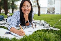 Nätt asiatisk kvinnlig student som tar anmärkningar som ligger på rutiga plommoner Royaltyfri Foto