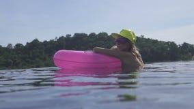 Nätt bärande bikini för ung kvinna, gul hatt och purpurfärgad solglasögon som simmar med den rosa uppblåsbara cirkeln i oändlighe lager videofilmer